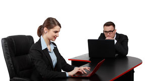 Young Business Couple on Laptops. Young business colleagues working on their laptops at the office desk, isolated against a white background.The focus is Royalty Free Stock Photography