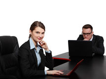 Young Business Couple on Laptops. Young business colleagues working on their laptops at the office desk, isolated against a white background.The focus is Royalty Free Stock Photos