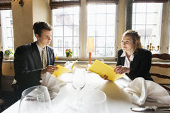 Young business couple with menus at restaurant table Stock Photos
