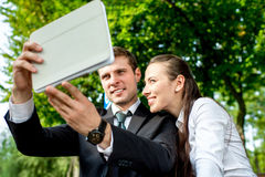 Young Business couple outdoors. Young Business couple sitting on the bench and making selfie photo with tablets Stock Photo