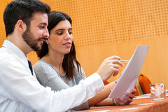 Young business couple reviewing documents in conference hall. Royalty Free Stock Photos