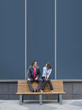 A young business couple sitting on a bench Royalty Free Stock Image