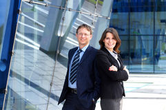 A young business couple standing in formal clothes. A young Caucasian business couple standing in formal clothes. The image is taken on a modern architectural Royalty Free Stock Photo