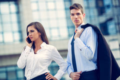 Young Business Couple. Standing in front of office buildings and business women talking by mobile phone Royalty Free Stock Image