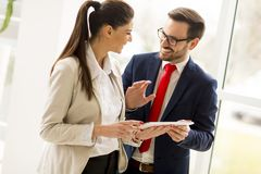 Young business couple with tablet in the office. Young business couple with tablet in the modern office Royalty Free Stock Images