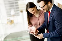 Young business couple with tablet in the office. Young business couple with tablet in the modern office Stock Photos
