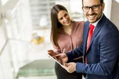 Young business couple with tablet in the office. Young business couple with tablet in the modern office Stock Image