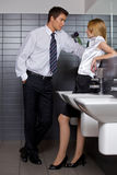 Young business couple talking intimately in office washroom Royalty Free Stock Photography
