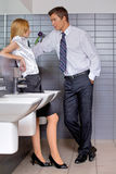Young business couple talking intimately in office washroom Royalty Free Stock Photos