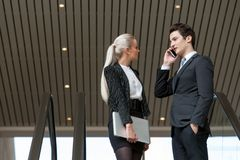 Business couple talking on phone in mall. Royalty Free Stock Photo