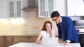 Young business couple talking and using tablet in kitchen at home. Young business couple talking and using tablet in kitchen at home stock video footage