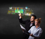 Young business couple touching colorful charts and diagrams Royalty Free Stock Images