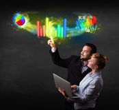 Young business couple touching colorful modern graph system conc Royalty Free Stock Images