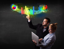 Young business couple touching colorful modern graph system conc Stock Photography
