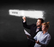 Young business couple touching web browser address bar with www Stock Photos
