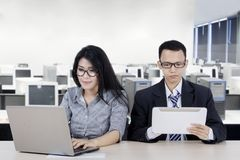 Young business couple using digital device. Portrait of young business couple using digital device while working in the office Royalty Free Stock Photo