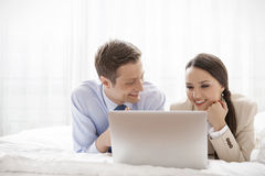 Young business couple using laptop in hotel room Stock Photo