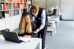 Young business couple using laptop in the office. View at young business couple using laptop in the office Royalty Free Stock Photos