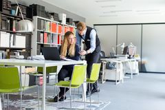 Young business couple using laptop in the office. View at young business couple using laptop in the office Stock Photography