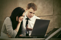 Young business couple using laptop outdoor Stock Images
