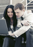 Young business couple using laptop on the steps Stock Photo