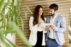 Young business couple using tablet in the office. Young business couple using tablet in the modern office Royalty Free Stock Image