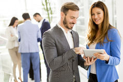 Young business couple using tablet in the office. View at young business couple using tablet in the office Royalty Free Stock Photography