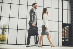 Young business couple walking near the office building. Young business couple walking outdoor near the office building Royalty Free Stock Photography