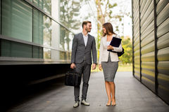 Young business couple walking outdoors. Young business couple walking outdoor near the office building Royalty Free Stock Photo