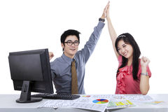 Young business couple winning. With computer on the desk royalty free stock image
