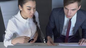 Young business couple is working front of computer, man and woman discussing new project 4k , sitting at desk, reading. Young business couple is working front of stock video footage