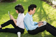 Young business couple. Working on laptop and digital tablet in the park Stock Photos