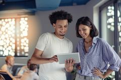 Young business couple working on tablet in modern office royalty free stock photography