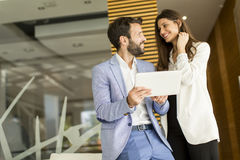 Young business couple working on tablet. In modern office Stock Photography