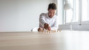 Young business executive positioning white chess pieces in a sensible structure. On his office desk in a conceptual image of company structure and human stock image