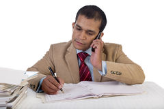 Young Business Executive at Work and talking on phone while at his desk amidst a pile of files. Royalty Free Stock Images