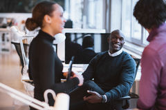 Young business executives during break. Happy african men sitting at desk with coworkers smiling. Young business executives during break stock photography