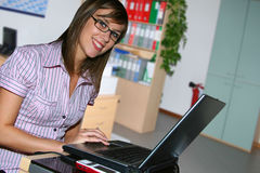 Young business girl. Young business with laptop in office Stock Photography