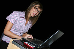 Young business girl. Young business with laptop and mobile phone on black background Stock Photography