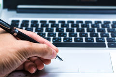 Young business hand writing in a laptop Stock Photography