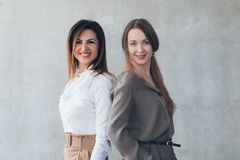 Young business ladies smiling friends colleagues. Young business ladies. Friends corporate colleagues back to back. Smiling confident smart successful company stock photos