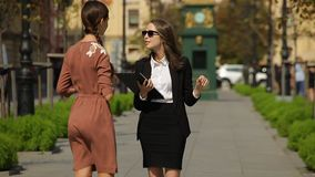 Young business lady describes a real estate object to her client in a park. Cheerful female real estate agent, with stylish long hair, in black sun glasses stock footage