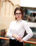 Young business lady in glasses posing while standing indoor Royalty Free Stock Photography