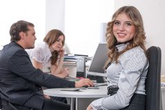 Young business lady smiling in office. Attractive business lady sitting and smiling over colleagues background in office Royalty Free Stock Image