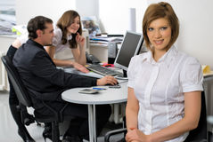 Young business lady smiling in office. Attractive business lady sitting and smiling over colleagues background in office Stock Photo