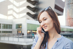 Young business lady is talking on smart-phone and smiling with her teeth. Stock Photo