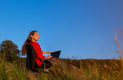 Young business lady thoughtfully looks towards solar rising or s Stock Photos