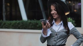 Young business lady using mobile phone near business center. Woman using mobile phone for business communication voice stock footage