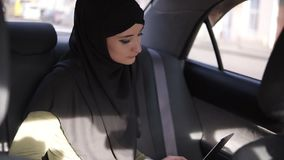 Young business lady wearing grey head scarf hijab using laptop on the back seat in car. Arabic woman typing on laptop. Works from the car. Using technologies stock footage