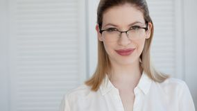 Young business lady in white shirt and glasses. Attractive young woman smiling royalty free stock image